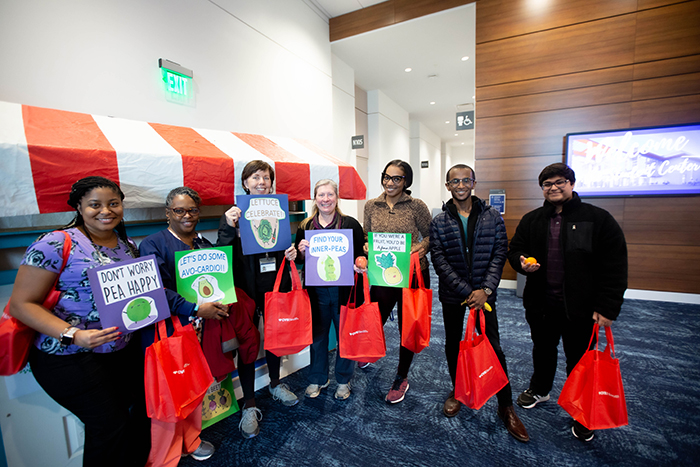 A group of employees pose with their freebies and signs with phrases about fruits and vegetables