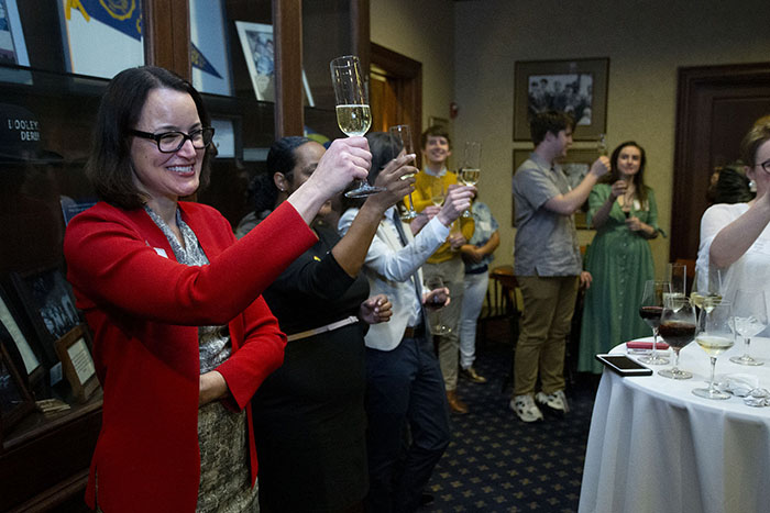 A woman raises a glass for a toast at the Pride Awards