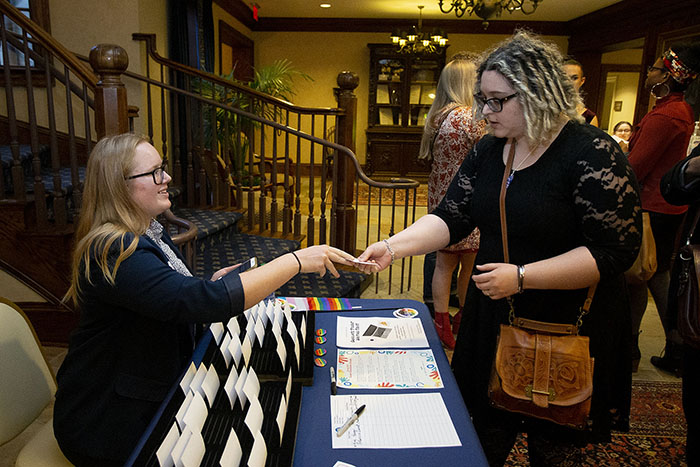 A woman hands another woman her name tag at a table at the Pride Awards