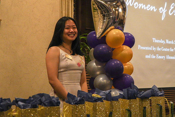 A young woman smiles from behind a table for the Women of Excellence Awards