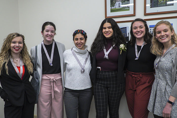 A group of woman pose for a photo while wearing matching ribbons around their necks for the Women of Excellence Awards
