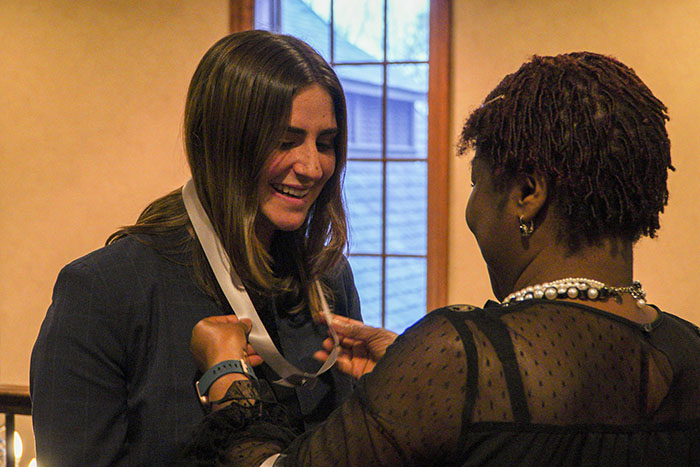 A woman puts a ribbon around another young woman's neck for the Women of Excellence Awards