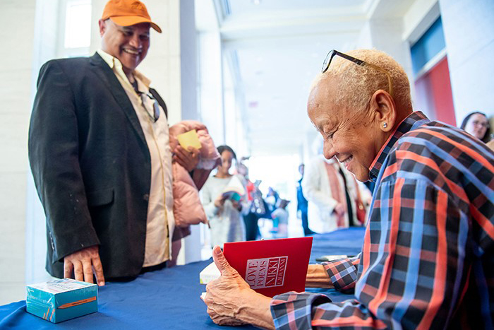 Nikki Giovanni signs a book for a fan