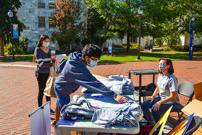 Students in masks give out t-shirts on the quadrangle