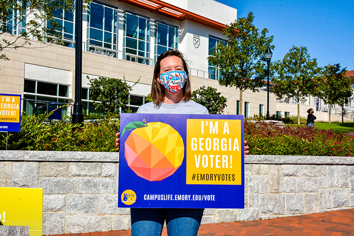 "A student wearing a mask holds up a sign that says: ""I'm a Georgia voter"""
