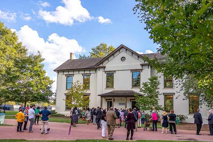 A group of Oxford community members stand outside of Johnson Hall on a sunny day