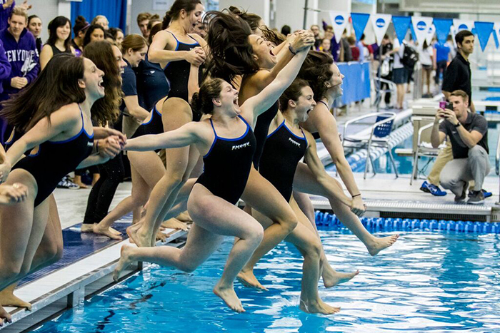 women swimmers jump into the pool in celebration