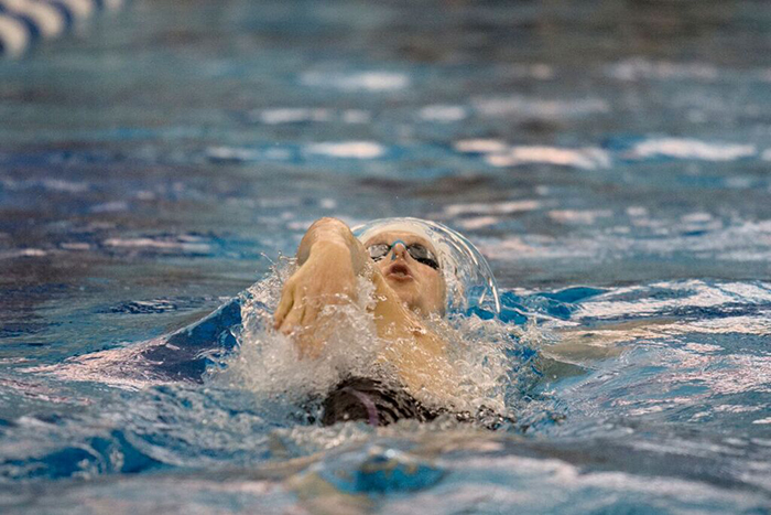 male swimmer competes in backstroke