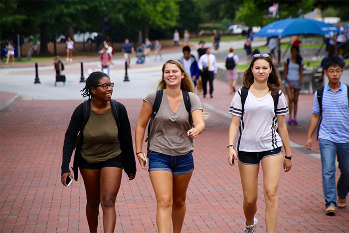 three women walking on campus