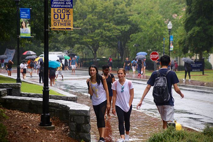 people walking in rain on campus