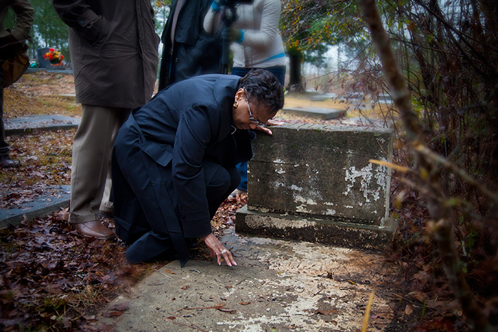 Seeing her father's grave for the first time, Dorothy Nixon Williams bent to touch the marker etched with his name before weeping in the arms of her son.