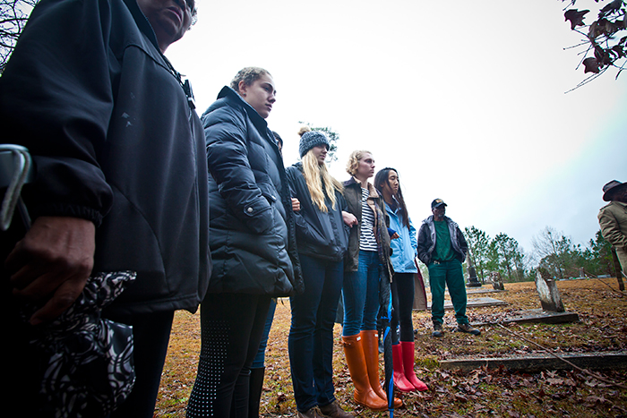 Students linked arms as they stood in the light rain watching as Dorothy Nixon Williams saw her father's grave.