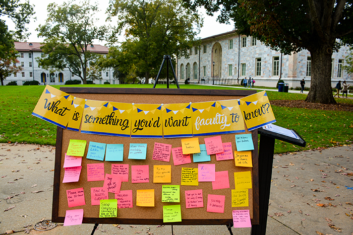 "A bulletin board with colorful sheets of paper on it reads, ""What is something you'd want faculty to know?"""