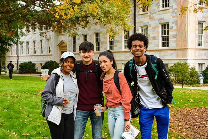 Four students pose on the quad