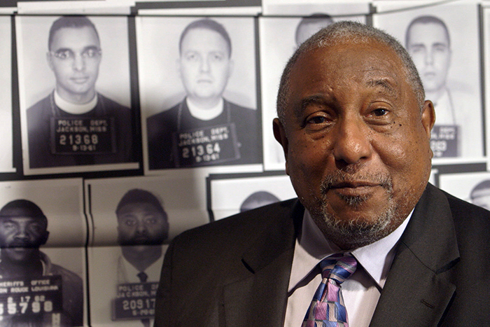 Bernard LaFayette speaks to the camera during a filming for the course at the Center for Civil and Human Rights. His mugshot, taken after his arrest during the Freedom Rides in June 1961, appears in the top row at the far left of this image.