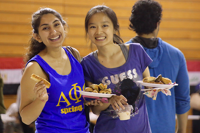 Two females with plates of food in their hand