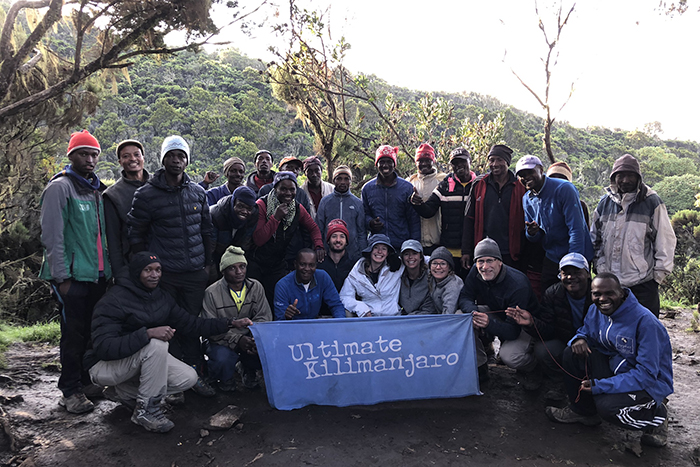 A large group holds a banner that reads 'Ultimate Kilimanjaro'