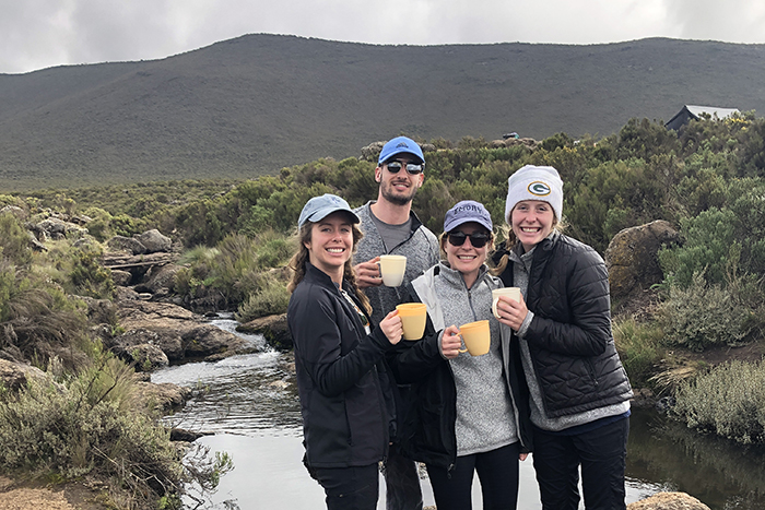 Four hikers hold coffee mugs in front of the mountain