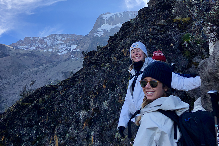 Two hikers pose smiling while on the mountain trail