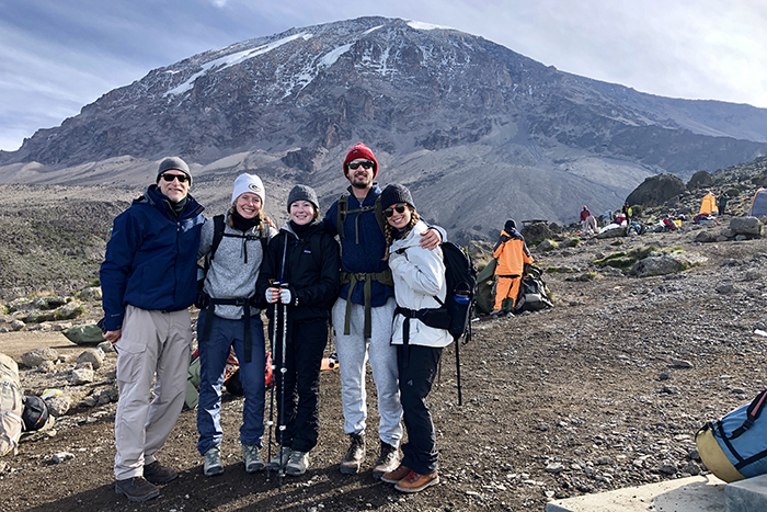 The group of hikers stand in front of their camp site with Mount Kilimanjaro in the distance