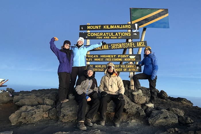 Five people stand at the Mount Kilimanjaro summit in front of a sign congratulating them