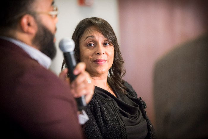 "Natasha Trethewey listens as Kevin Young speaks at the ""Neil Asks"" event."