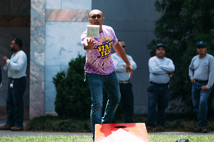 Staff members play corn hole at Staff Fest