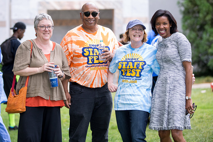 Staff members pose with Emory President Claire E. Sterk
