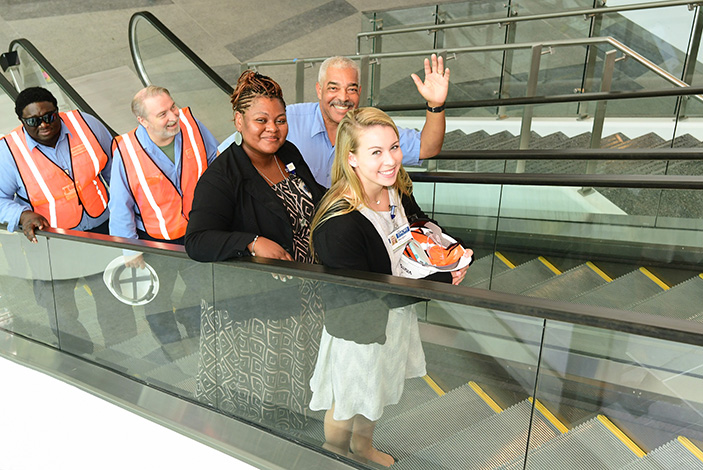 Employees test out the new escalator in the Emory University Hospital Tower between the first and second floors.