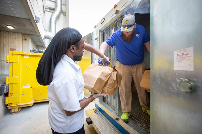 Workers delivering meal bags