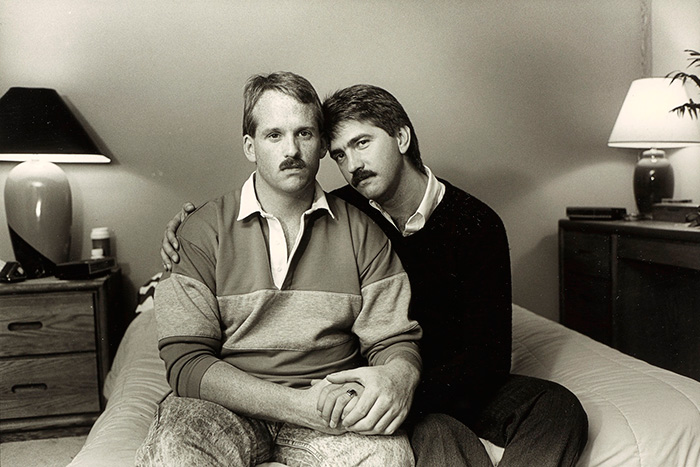 Two men sitting on a bed, one with an arm around the other