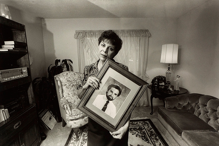 Woman holding picture of younger man