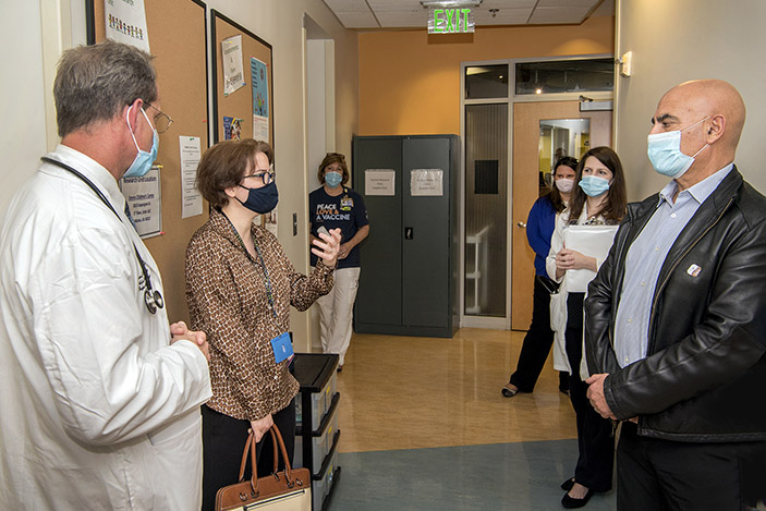 Nadine Rouphael speaks to Moncef Slaoui at the Emory Children's Center as Evan Anderson and other clinic staff members look on.