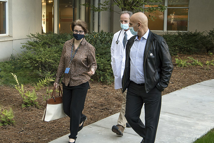 Moncef Slaoui walks with Nadine Rouphael and Evan Anderson outside the Emory Children's Center