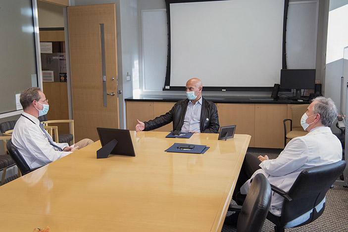 Moncef Slaoui speaks to Evan Anderson about the status Operation Warp Speed in a conference room at the Emory Children's Center. David S. Stephens looks on.