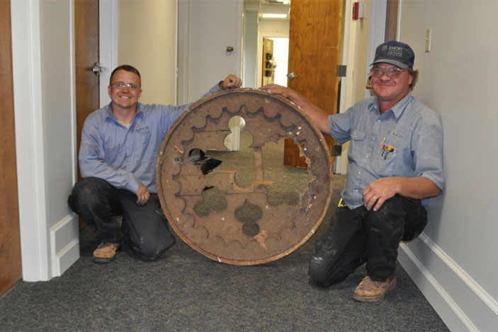 Gary Brown (left) and Al Mitchell, of Oxford's facilities management team, are seen holding a handmade, decorative cover that fit the gable vent on the building's north side. Using photographs to confirm that it was used in the building, the cover was restored, and it is now back in its original place.