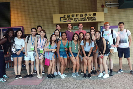 Four Emory undergraduates pose with their cohort of academic interns this summer in Hong Kong.