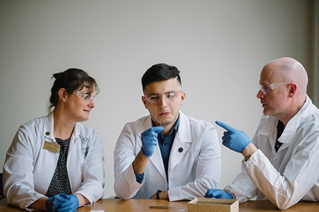 Emory College junior Kasey Cervantes (center) holds a tiny mosquito specimen like the hundreds he is helping catalog at the Natural History Museum in London. His summer research came about through a collaboration between Emory nursing professor Helen Baker (left) and CDC research entomologist Seth Irish (right). Emory Photo/Video